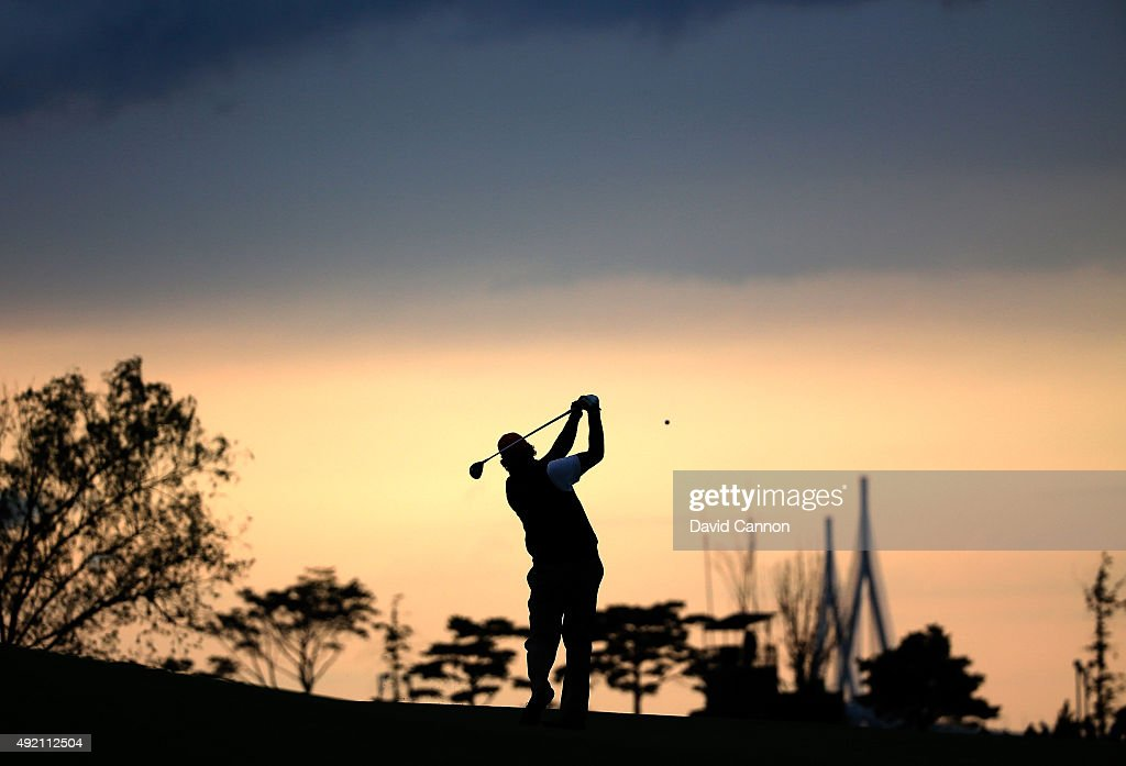 Phil Mickelson of the United States team plays his second shot on the 15th fairway as the sun sets during the Saturday afternoon fourball matches at The Presidents Cup at Jack Nicklaus Golf Club Korea on October 10, 2015 in Songdo IBD, Incheon City, South Korea.