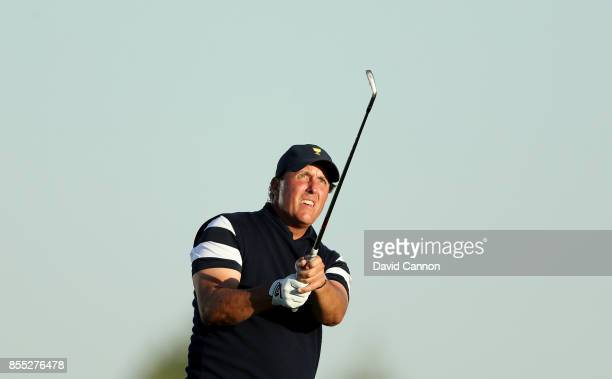 Phil Mickelson of the United States team plays his second shot on the 17th hole in his match with Kevin Kisner against Jason Day and Marc Leishman of...