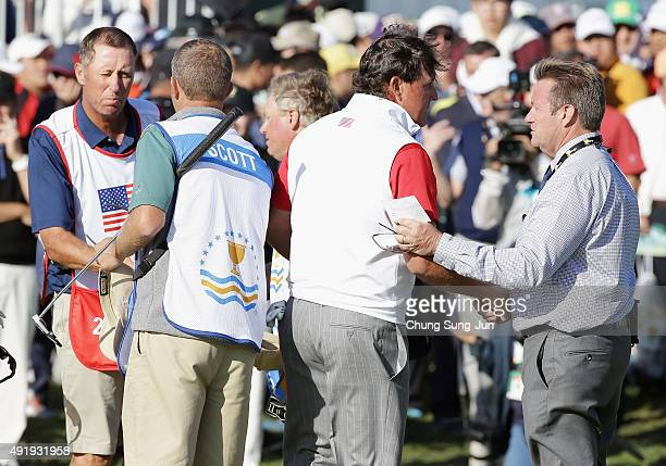 Phil Mickelson of the United States Team shakes hands with rules offical Gary Young on the 18th green during the Friday four-ball matches at The...