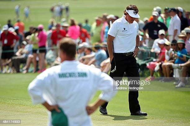 Phil Mickelson of the United States walks on the 18th green during the second round of the 2014 Masters Tournament at Augusta National Golf Club on...