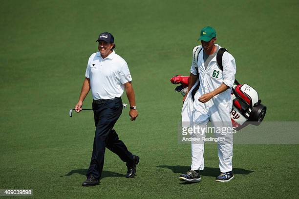 Phil Mickelson of the United States walks to the second green alongside his caddie Jim Mackay during the first round of the 2015 Masters Tournament...