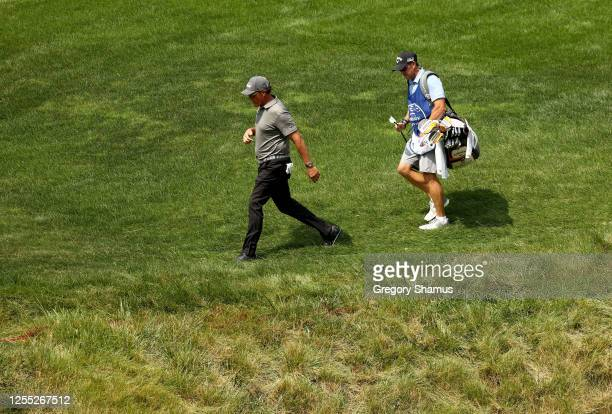 Phil Mickelson of the United States walks with his caddie and brother Tim Mickelson on the 11th hole during the first round of the Workday Charity...