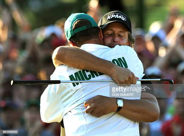 Phil Mickelson of the US hugs his caddie Jim 'Bones' Mackay after sinking his putt on the 18 hole to win the 2010 Masters Tournament at Augusta...