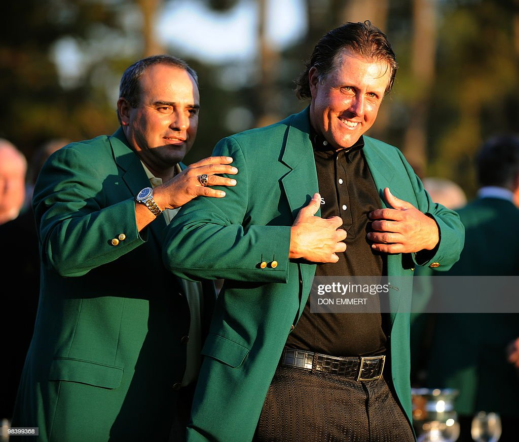 Phil Mickelson of the US receives his green jacket from last years winner Angel Cabrera of Argentina (L) after winning the 2010 Masters Tournament at Augusta National Golf Club on April11, 2010 in Augusta, Georgia. The 39-year-old left-hander finished 72 holes on 16-under par 272.