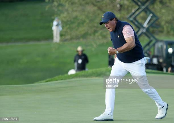 Phil Mickelson of the US Team celebrates on the 18th green after he and Kevin Kisner of the US Team defeated Marc Leishman of Australia and the...