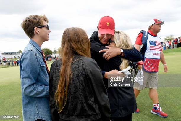Phil Mickelson of the US Team embraces his wife Amy Mickelson alongside son Evan Mickelson and daughter Sophia Mickelson during the Saturday morning...
