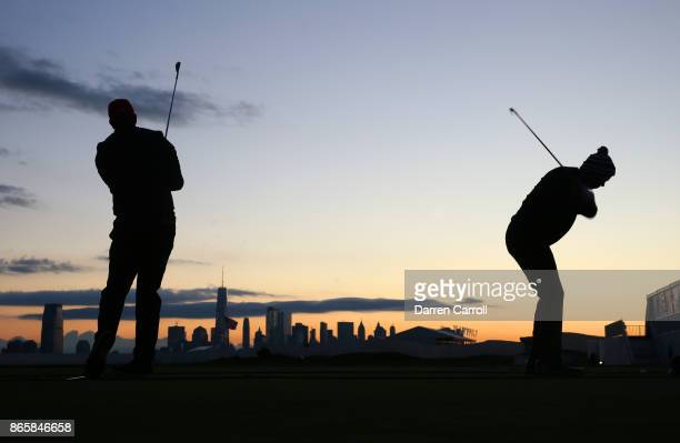 Phil Mickelson of the US Team left and Matt Kuchar of the US Team right warms up on the range as the sun rises during the third round of the...