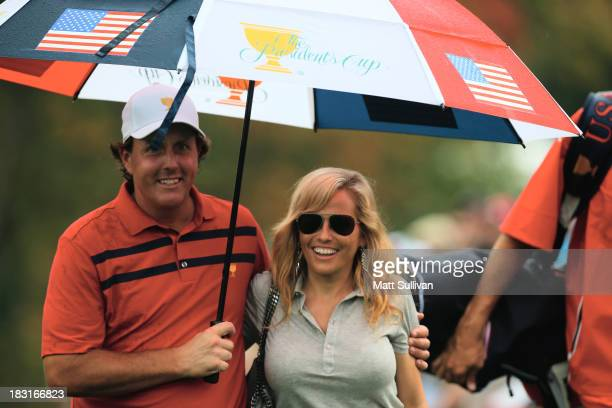 Phil Mickelson of the US Team waits under an umbrella with his wife Amy during the Day Three Fourball Matches at the Muirfield Village Golf Club on...