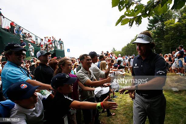Phil Mickelson of the USA greets fans during the first round of the Deutsche Bank Championship at TPC Boston on August 30, 2013 in Norton,...