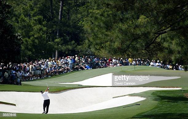 Phil Mickelson of the USA plays out of the bunker on the first hole during the third round of the Masters at the Augusta National Golf Club on April...