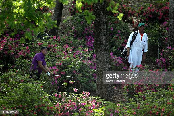 Phil Mickelson of the USA plays out of the woods on the par five 13th hole during the first round of the 2011 Masters Tournament at Augusta National...