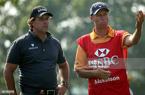 Phil Mickelson of the USA waits with his caddie Jim 'Bones' Mackay on the 12th hole during the first round of the WGCHSBC Champions at Sheshan...