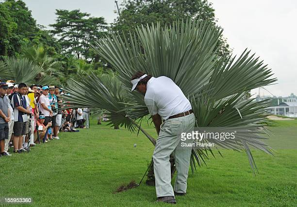 Phil Mickelson of USA plays a shot from behind a bush on the seventh hole during the resumption of the rain delayed second round of the Barclays...