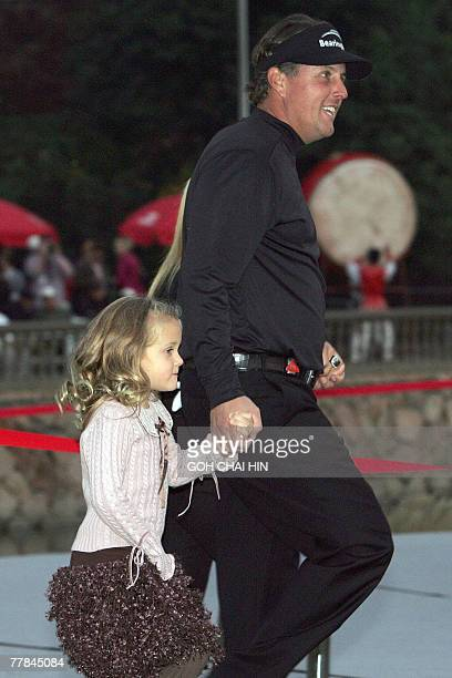 Phil Mickelson of USA with his daughter Sophia Isabel as he makes his way to the awards ceremony of the fivemillionUSD HSBC Champions tournament in...