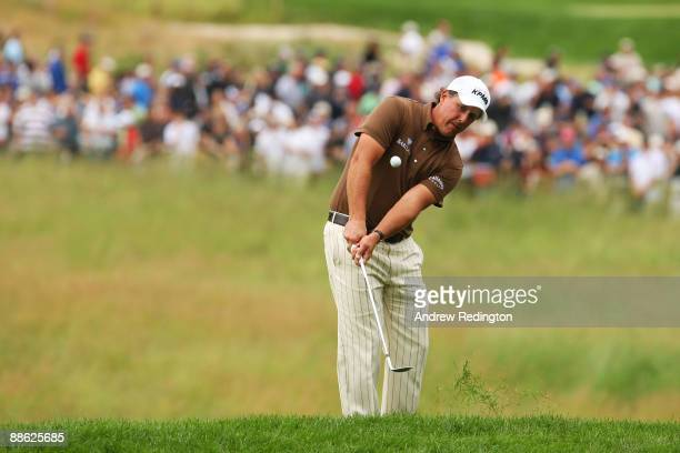 Phil Mickelson pitches to the 17th green during the continuation of the final round of the 109th US Open on the Black Course at Bethpage State Park...