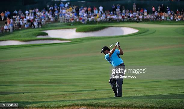 Phil Mickelson plays a shot from the fairway on the 18th hole in front of a gallery during round two of the 90th PGA Championship at Oakland Hills...