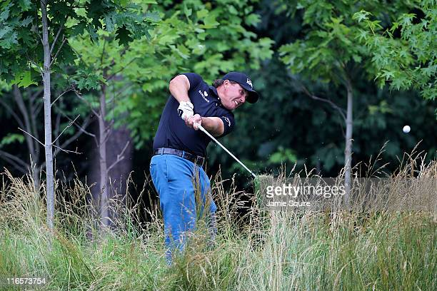 Phil Mickelson plays his second shot from the deep rough on the 14th hole during the first round of the 111th US Open at Congressional Country Club...