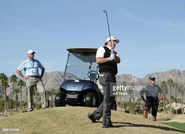 Phil Mickelson plays his second shot on the 14th hole as swing coach Andrew Getson and caddie Tim Mickelson look on during practice for the...