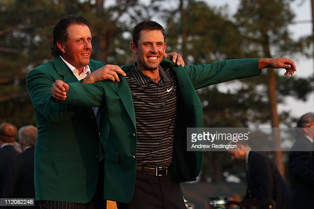 Phil Mickelson presents Charl Schwartzel of South Africa the winner's jacket at the green jacket presentation after Schwartzel's twostroke victory at...