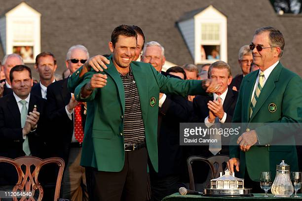 Phil Mickelson presents Charl Schwartzel of South Africa the winner's jacket at the green jacket presentation as William Porter Payne looks on after...