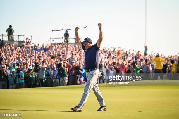 Phil Mickelson raises his arms and celebrates his two stroke victory on the 18th hole green during the final round of the PGA Championship on The...