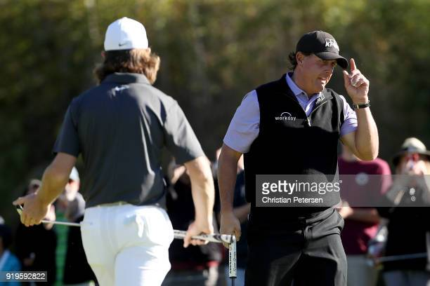 Phil Mickelson reacts after making eagle on the first green as Tommy Fleetwood of England walks past during the third round of the Genesis Open at...