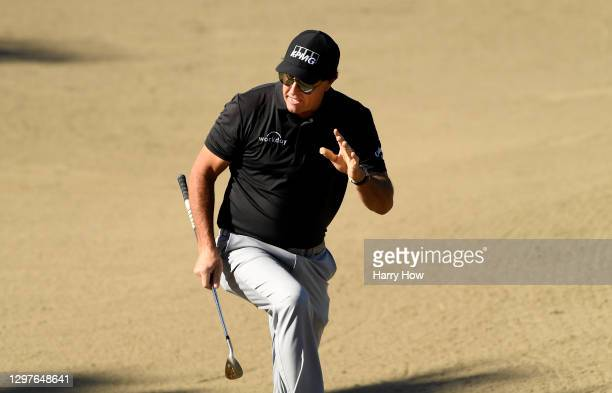 Phil Mickelson reacts to his shot out of the bunker on the 11th hole during the first round of The American Express tournament on the Jack Nicklaus...