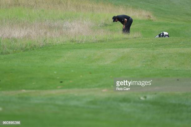 Phil Mickelson searches for his ball on the 14th hole during round two of A Military Tribute At The Greenbrier held at the Old White TPC course on...