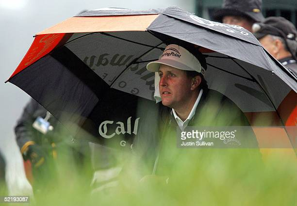 Phil Mickelson sits under an umbrella before teeing off on the fifth tee at Pebble Beach Golf Links during the ATT Pebble Beach ProAm National...