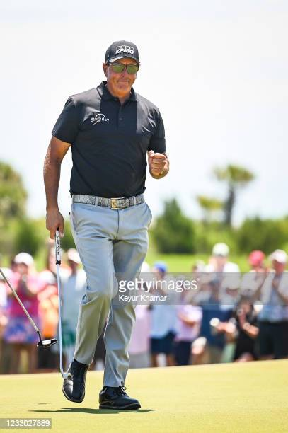 Phil Mickelson smiles and celebrates with a fist pump after making a birdie putt on the ninth hole green as Padraig Harrington of Ireland looks on...