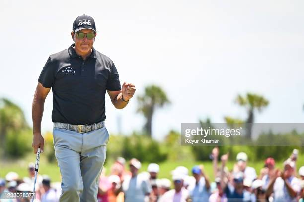 Phil Mickelson smiles and celebrates with a fist pump after making a birdie putt on the ninth hole green during the second round of the PGA...