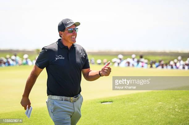 Phil Mickelson smiles and gives a thumbs up to fans after making a birdie putt on the ninth hole green during the second round of the PGA...