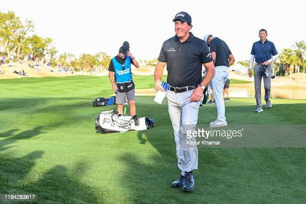 Phil Mickelson smiles at fans after finishing play on the ninth hole green during the second round of the The American Express on the Nicklaus...