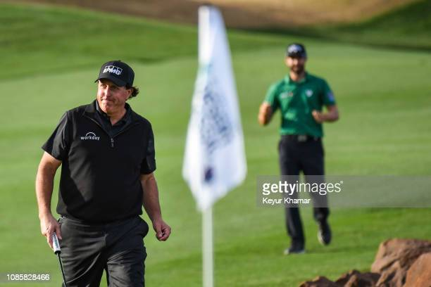 Phil Mickelson smiles at fans as he and Adam Hadwin of Canada walk to the 18th hole green during the final round of the Desert Classic on the Stadium...