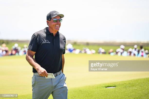 Phil Mickelson smiles with his scorecard in hand after making a birdie putt on the ninth hole green during the second round of the PGA Championship...