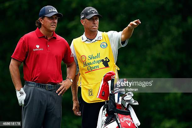 Phil Mickelson speaks with his caddies Jim 'Bones' Mackay on the sixth tee during the third round of the Shell Houston Open at the Golf Club of...