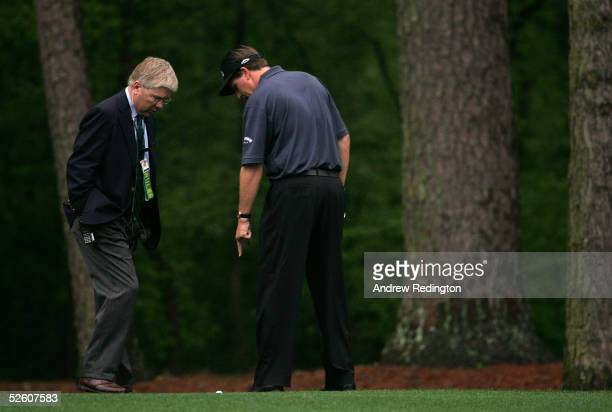 Phil Mickelson talks to a rules official on the 11th hole during round two of The Masters at the Augusta National Golf Club on April 9 2005 in...