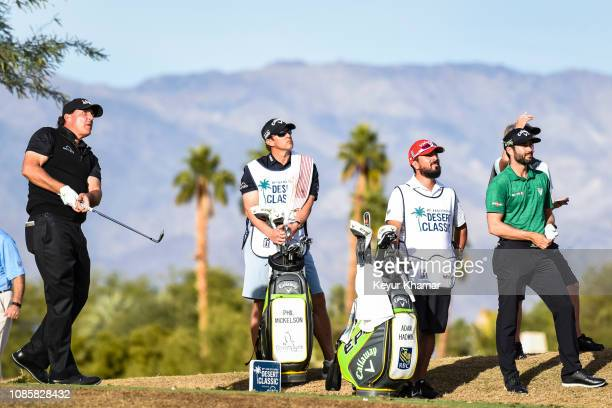 Phil Mickelson tees off on the 17th hole as Adam Hadwin of Canada looks on during the final round of the Desert Classic on the Stadium Course at PGA...