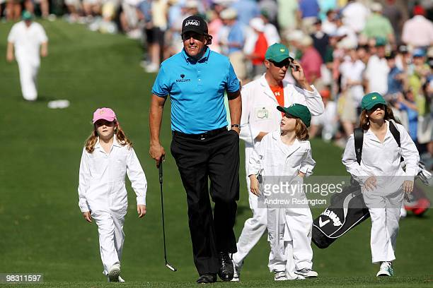 Phil Mickelson walks with his caddies daughter Sophia son Evan daughter Amanda and Jim MacKay during the Par 3 Contest prior to the 2010 Masters...