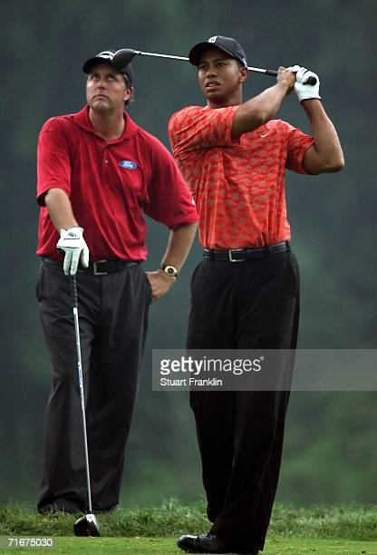 Phil Mickelson watches as Tiger Woods takes a practice swing before playing his tee shot on the 18th hole during the second round of the 2006 PGA...