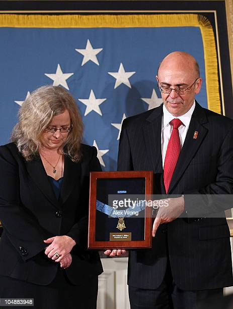 Phil Miller and Maureen Miller pray as they receive a Medal of Honor on behalf of their late son Army Staff Sergeant Robert J Miller during an East...