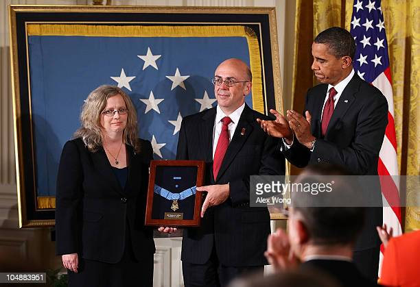Phil Miller and Maureen Miller receive a Medal of Honor on behalf of their late son Army Staff Sergeant Robert J Miller from US President Barack...