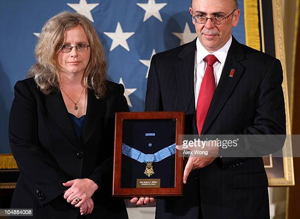Phil Miller and Maureen Miller receive a Medal of Honor on behalf of their late son Army Staff Sergeant Robert J Miller during an East Room ceremony...