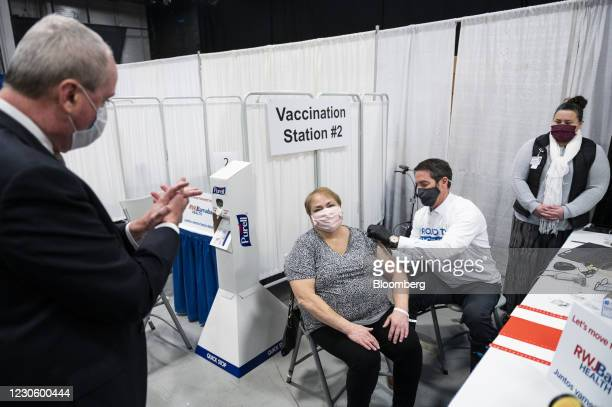 Phil Murphy, New Jersey's governor, left, applauds after a person receives a dose of a Covid-19 vaccination at the New Jersey Convention and...