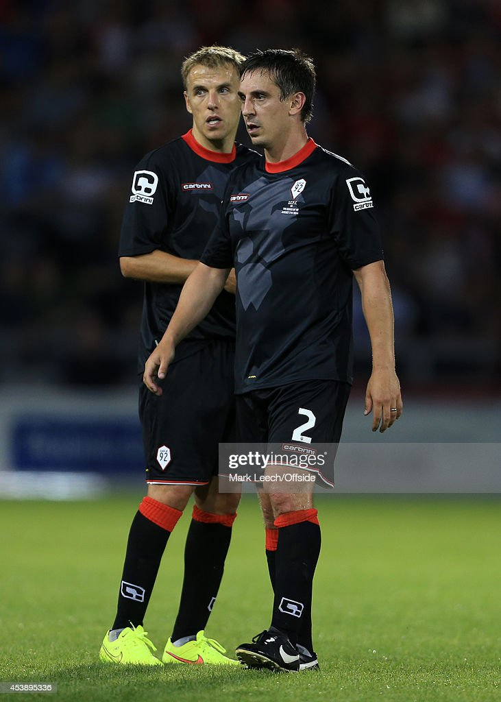Phil Neville (L) and brother Gary Neville seen together during the pre-season friendly match between Salford City and the Class of '92 at the AJ Bell Stadium on August 7, 2014 in Salford, England.