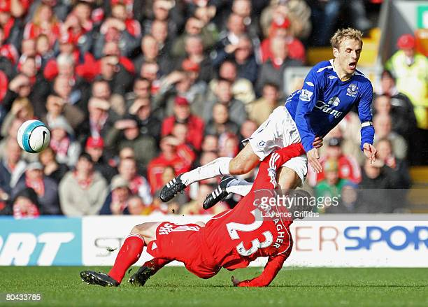 Phil Neville of Everton flies through the air as he is tackled hard by Jamie Carragher of Liverpool during the Barclays Premier League match between...