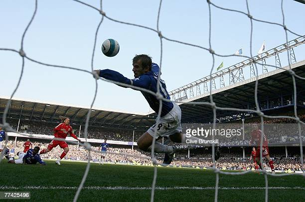 Phil Neville of Everton handballs on the line to give a penalty away for the winning goal which was scored by Dirk Kuyt of Liverpool during the...