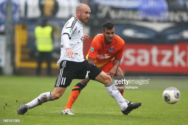 Phil OfosuAyeh of Duisburg is challenged by Marcel Schug of Elversberg during the Third Bundesliga match between SV 07 Elversberg and MSV Duisburg at...
