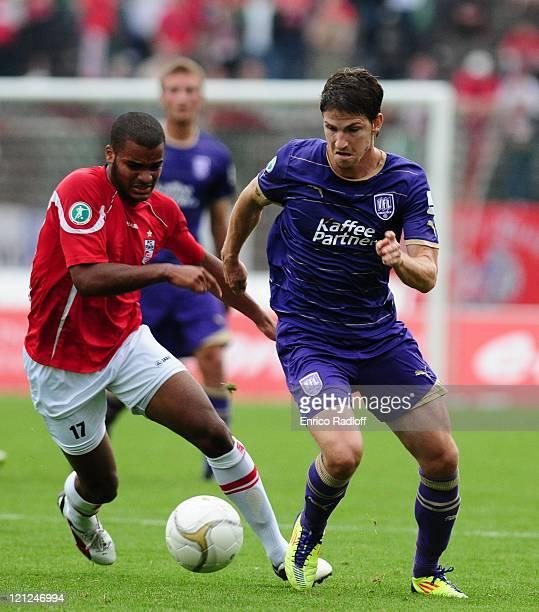 Phil OfosuAyeh of Rot Weiss Erfurt and Andreas Glockner of VFL Osnabrueck battle for the ball during the Third League match between RotWeiss Erfurt...