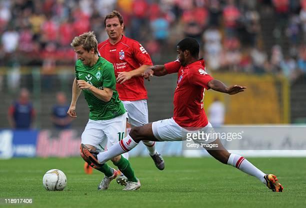 Phil OfosuAyeh of Rot Weiss Erfurt battles for the ball with Marko Marin of Bremen during the PreSeason friendly match between RotWeiss Erfurt and...